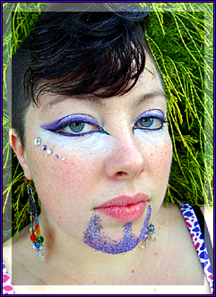 a photo of my face, wearing cat-eye makeup and a violet glitter goatee