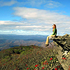 photo of Kat sitting on a rock outcrop overlooking a deep valley