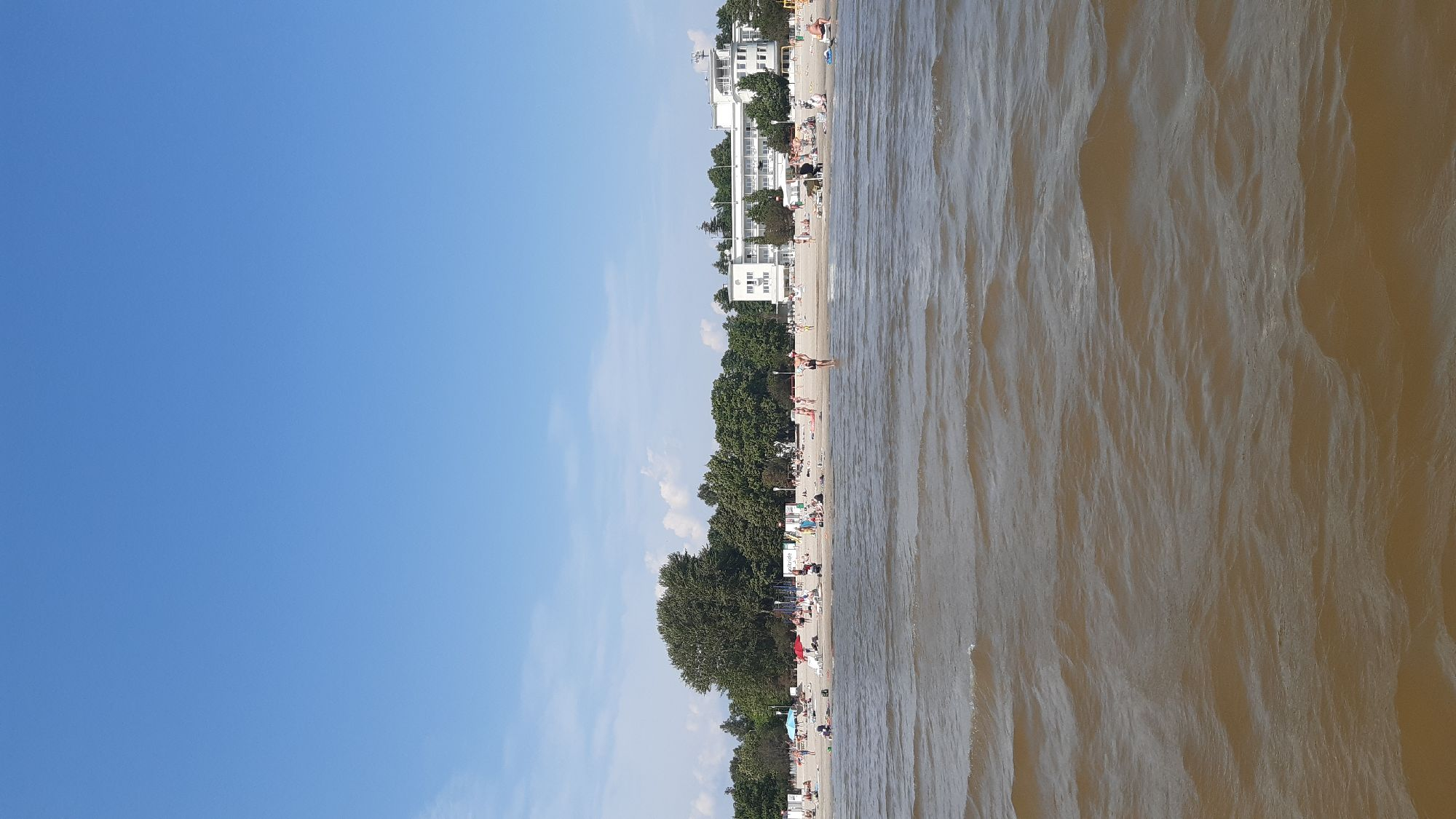 Вдалеке на пляже отель, в котором мы обедали.  А я снимаю, стоя по щиколотку в воде)