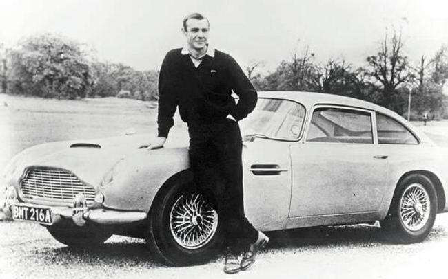 Шон-Коннери-в-роли-Джеймса-Бонда-позирует-рядом-с-Aston-Martin-DB5-1965-год