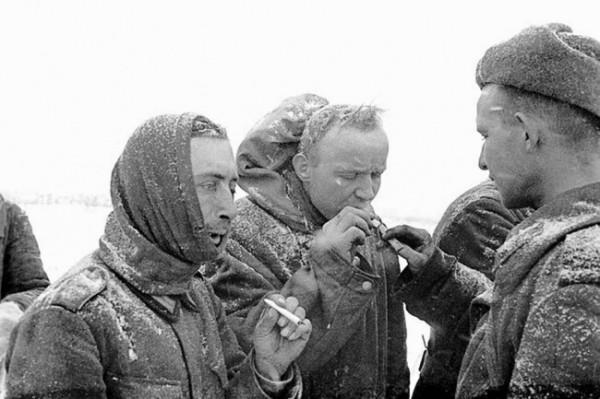 Советский боец дает прикурить пленным фашистам