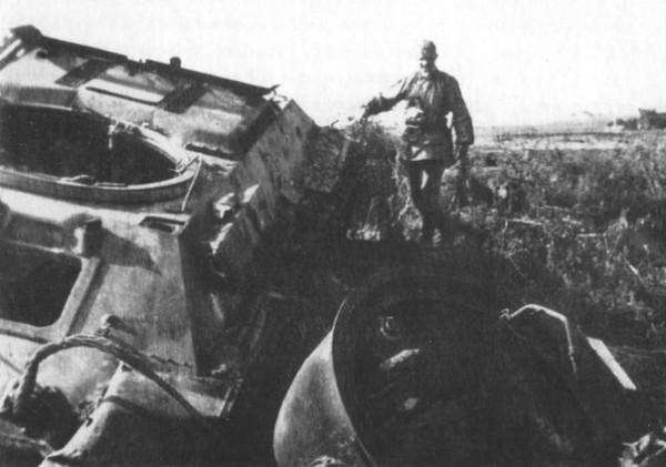 Немецкий солдат рассматривает советский танк Т-34 с сорванной башней