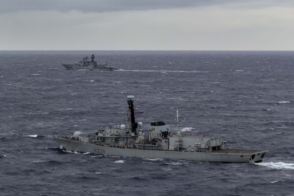 HMS Northumberland in the foreground monitors the Vice-Admiral Kulakov