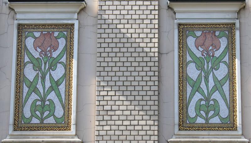 Мозаичные ирисы на фасаде между вторым и третьим этажами.