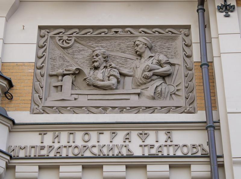 Барельеф, исполненный дрезденским скульптором, изображает двух типографских рабочих около печатного станка.