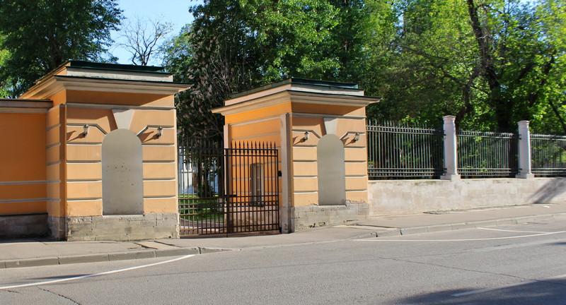 Металлическая ограда на белокаменных столбах и ворота на белокаменных пилонах.