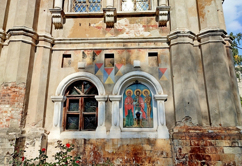 Храм Тихвинской иконы Божией Матери с Трапезной. Частично раскрыта покраска стен «в шахмат» и эксперименты реставраторов с подпором цветов последующей покраски фасада. Фото 2021.