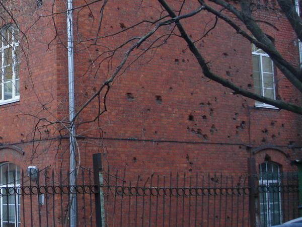 Следы разорвавшегося фугасного снаряда на стене бывшей лютеранской больницы.