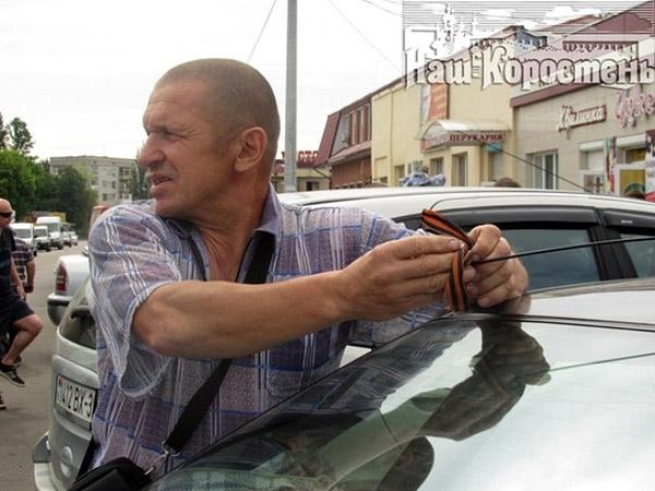 Белорус снимает черно-оранжевую ленточку с авто