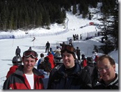 Brandon, Brad, and Ben at the Women's Grand Slalom races of the World Cup with a racer passing by in the background.