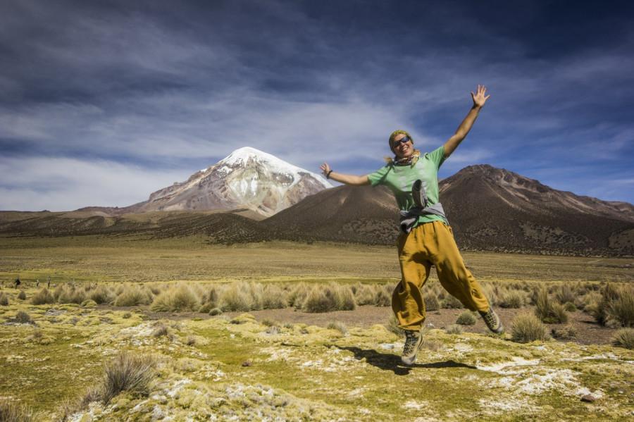 Девушка в прыжке на фоне вулкана Сахама в Боливии