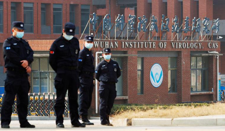 Тайная комната: сотрудники службы безопасности несут вахту за пределами WIV во время визита группы ВОЗ | Рейтер