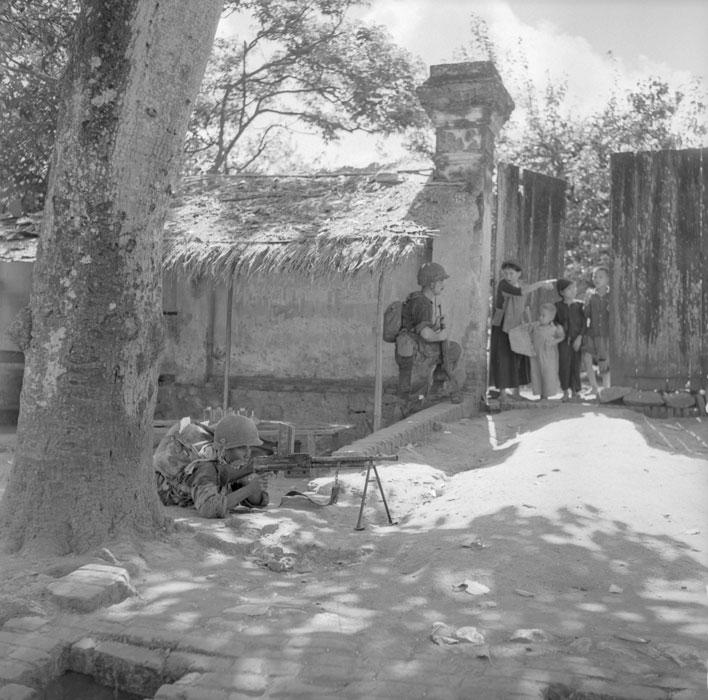 парашютист расспрашивает обитателей деревни о бойцах вьетминя