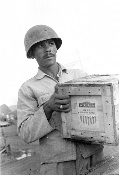 мужч несущий ящик с припасами из США 1950.jpg