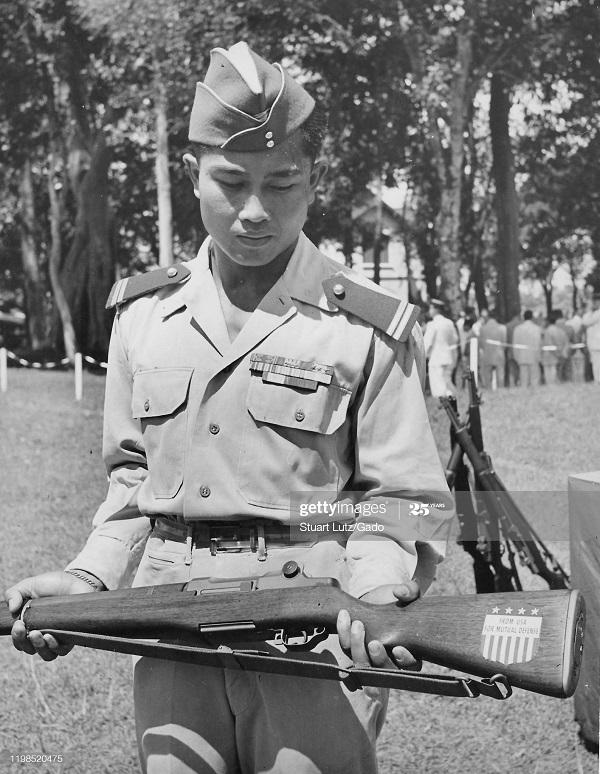 Военнослуж смотрит на приклад винтовки надпись Из США для взаимн защиты 1953 Стюарт Лютц.jpg