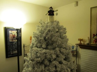 Flocked tree with snowman topper