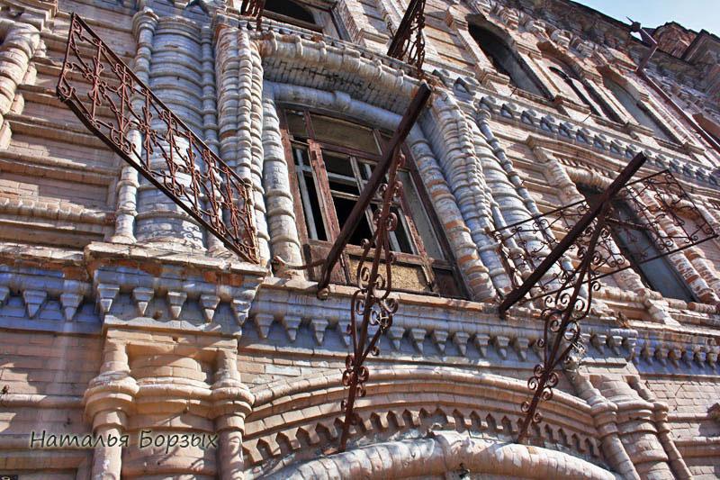 тёсаный кирпич в виде занавеса обрамляет окна второго этажа в центральной части
