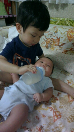 Jerry feeding Jerome when he was just a few months old using a milk storage container.