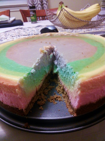 Rainbow cheesecake with a slice cut out