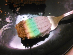 A bit of rainbow cheesecake resting on metal fork