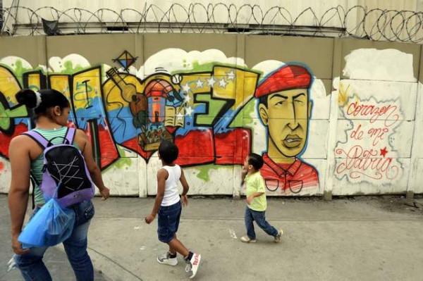 Люди проходят мимо стены с рисункомбольного президента Венесуэлы Уго Чавеса