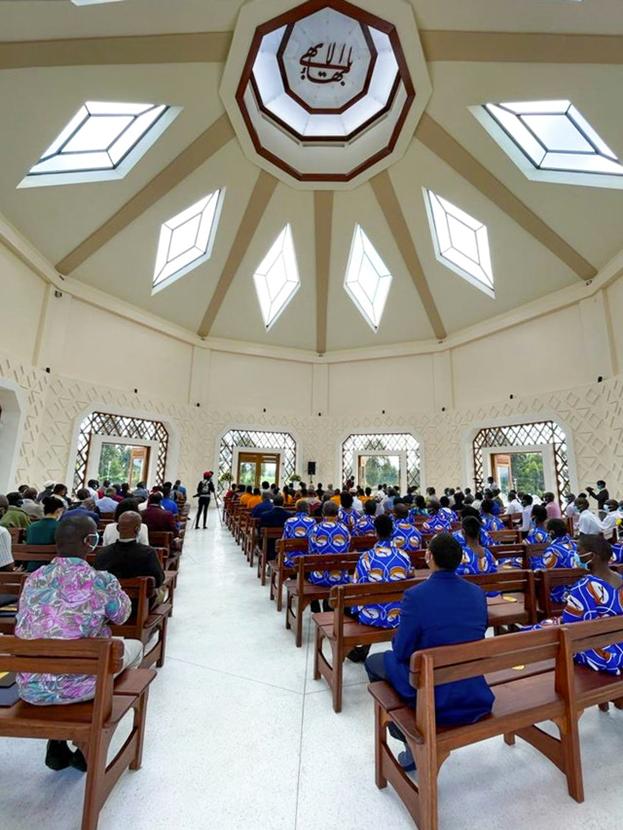 Присутствующие на церемонии посвящения сидят внутри центрального здания Храма, ожидая начала первой молитвенной программы.