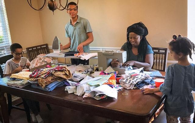 Молодёжь в Соединённых Штатах, активно участвующая в усилиях по построению общины бахаи, быстро откликнулись на множество потребностей, возникающих в своих общинах. На этом фото семья из Рокволла, штат Техас, готовит маски для своих соседей.