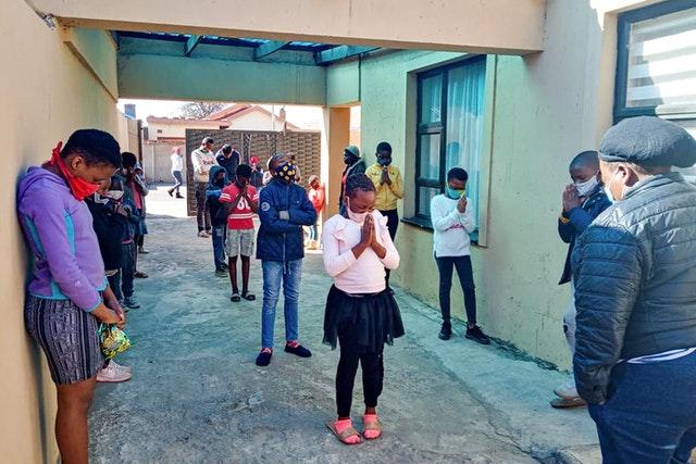 Группа молодёжи из Соуэто, Южная Африка, активно участвующая в усилиях по построению общины бахаи, молится вместе.