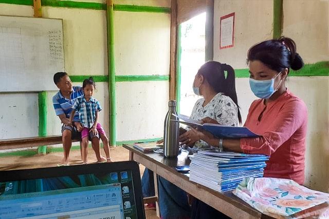 Учителя из общинной школы бахаи в Лангателе, Манипур, Индия, раздают родителям школьные задания, чтобы они выполняли их с детьми дома в качестве меры предосторожности во время эпидемиологического кризиса. Общинные школы, вдохновлённые принципами бахаи, нередко действуют в местах с ограниченной доступностью Интернета, поэтому они нашли творческие способы адаптироваться к нынешним обстоятельствам и удовлетворить образовательные потребности своих учеников.