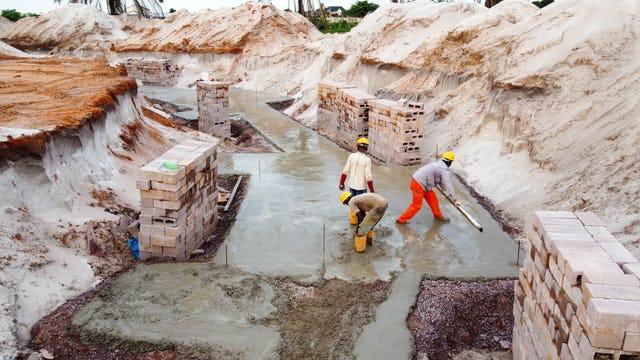 Процесс, известный как бетонная стяжка, создаёт гладкую поверхность для последующей работы. Затем с помощью каменных блоков выкладывается опалубка для железобетонных элементов фундамента.