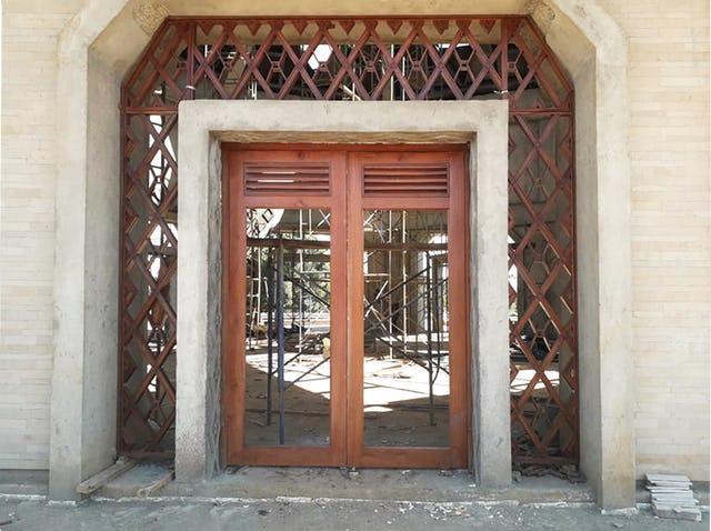 Один из девяти входов в центральное здание. Решётка вокруг каждого дверного проёма имеет конструкцию в виде стекла между двумя слоями дерева. Завершена отделка декоративной штукатуркой внешних колонн и дверных проёмов.