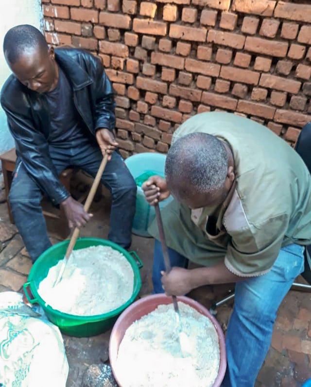 Санитарный инструктор обучает местных жителей приготовлению питательной мучной смеси.