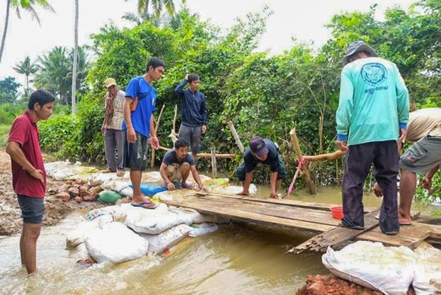 Члены общины в Окчи восстанавливают разрушенный после сильного наводнения мост.