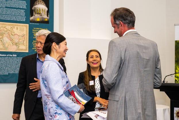 Очные встречи проводятся в соответствии с мерами безопасности, установленными правительством. Цзин Ли (слева), помощник премьер-министра штата Южная Австралия, беседует с представителями общины бахаи на встрече в Аделаиде, Южная Австралия.