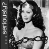 Wonder Woman, chained to a chair, seems wryly amused; caption along left side: '...seriously?' (black&white)