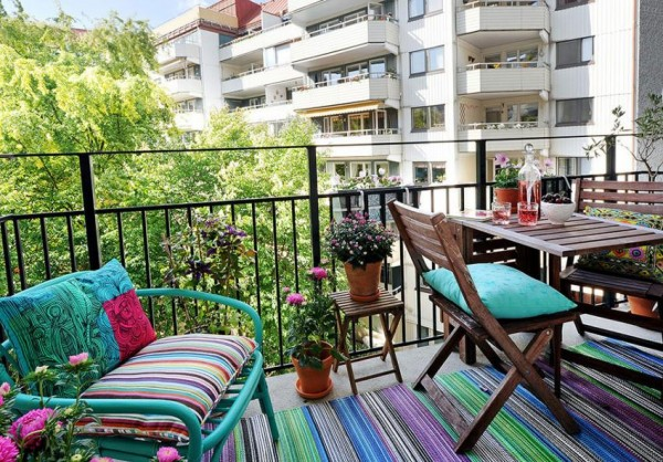 Colorful-balcony-decoration-with-stripes-fabric-with-wooden-table-and-coffee-table-in-terrace