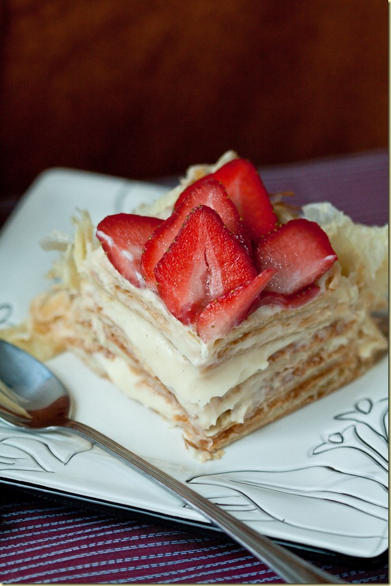 Slice of cake topped with strawberries on a white decorative plate.