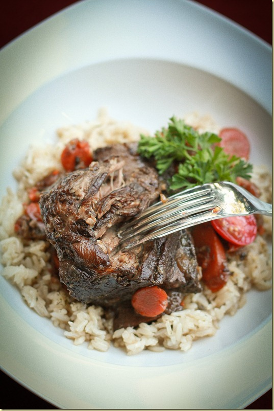 Short ribs in a bowl with carrots and tomatoes being spread with a fork.