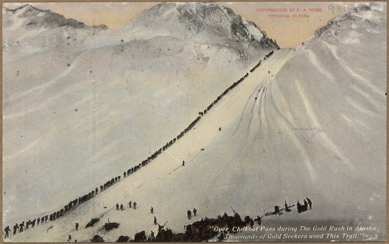 1280px-Color_post_card._'Over_Chilkoot_Pass_during_the_Gold_Rush_in_Alaska._Thousands_of_gold_seekers_used_this_trail.'_-_NARA_-_297823