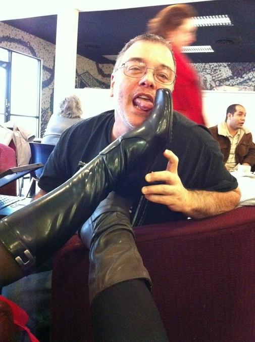 John licking Sarah's boot, which is crossed over Anna's boot