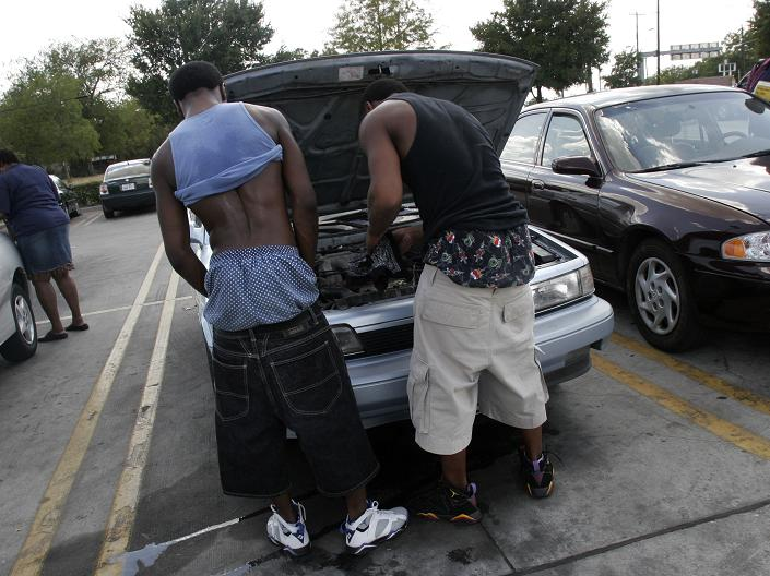 Two guys from the back with saggy pants on working under the hood of a car