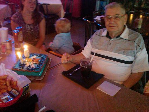 Dad with his birthday cake; Meagan and Ethan are in the background