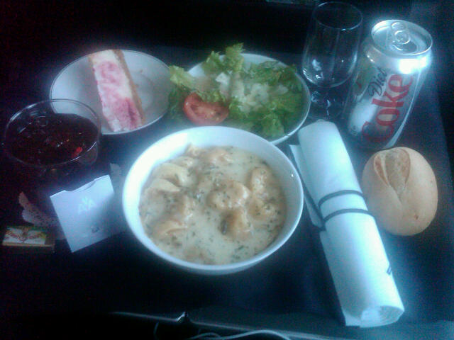 First Class dinner tray: mushroom tortellini, salad, strawberry cheesecake, and roll