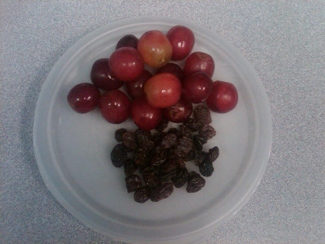 Grapes next to raisins on a plate