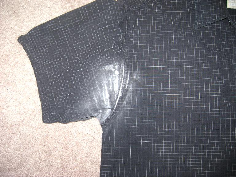 Close up of white stain under arm of short-sleeve black dress shirt