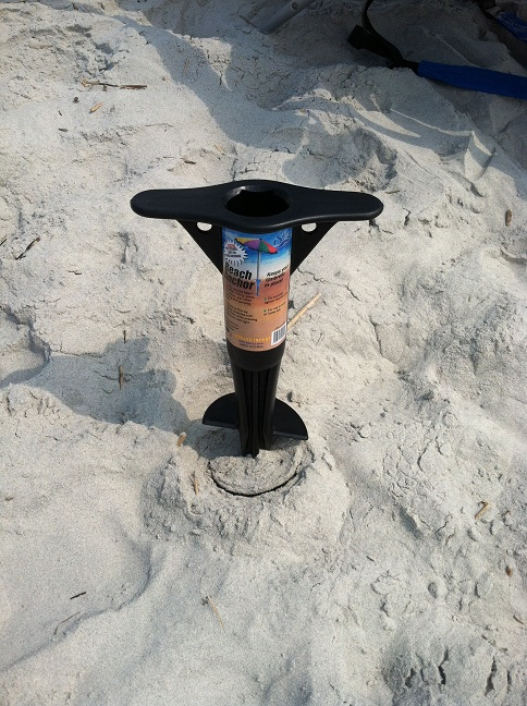 A screw-in black plastic 'beach anchor' that holds an umbrella