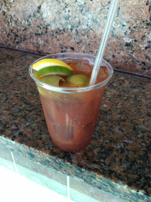 A Bloody Mary, complete with a lemon, a lime, and two big fat green olives sitting on the swim-up bar shelf