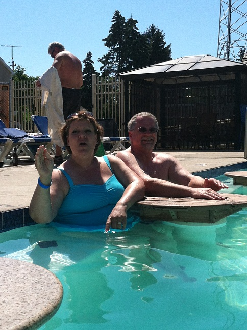 Pat, doing the queen's wave and John in the Splash Bar pool at a table