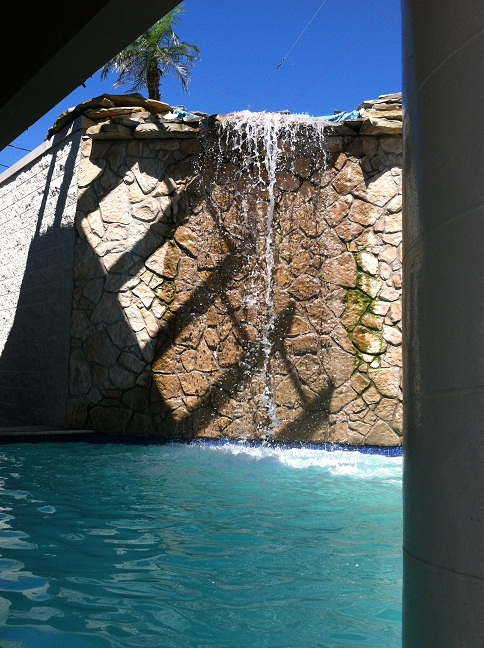A rock wall with a waterfall spilling over it into the pool