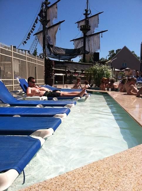 Lounge chairs in a shallow part of the pool with a pirate ship in the background